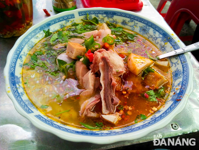 A mixed bowl of 'banh canh' features such various ingredients as fish cakes, meat on the bone and quail eggs.