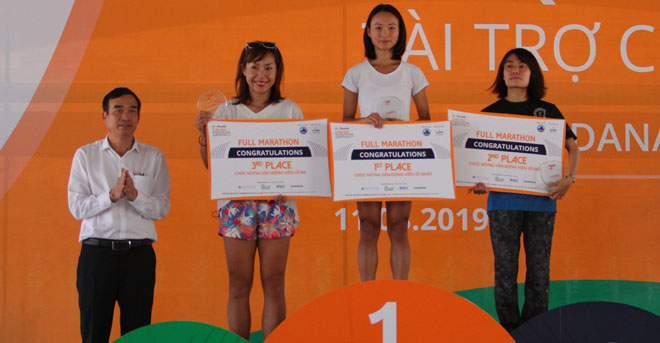 Municipal People's Committee Vice Chairman Chinh (left) presenting prizes to top 3 finishers in the full marathon for women