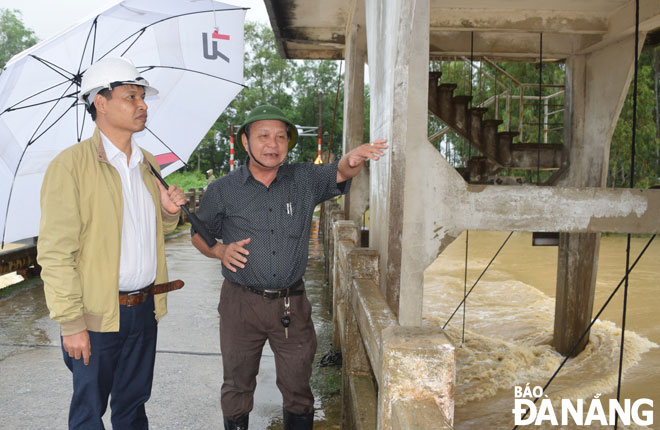 Municipal People's Committee Vice Chairman Ho Ky Minh city (left) checking the process of rainwater drainage at the An Trach Dam