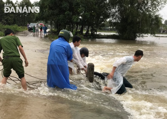 The retrieving of a broken-down motorbike swept away by strong rainwater inflows in Hoa Vang District