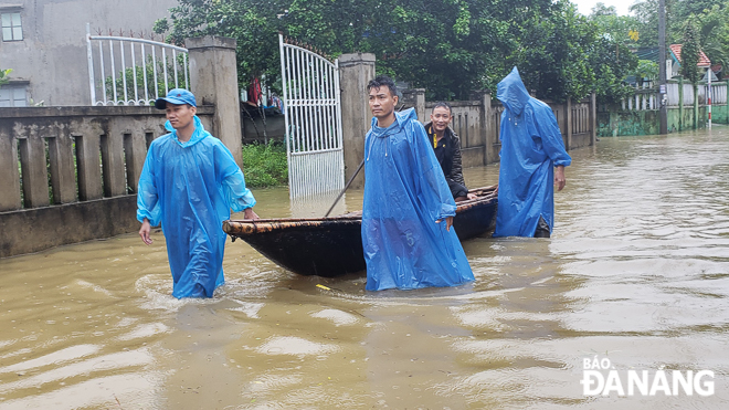 Local residents using boats to get through a massive volume of floodwaters in Hoa Phong Commune