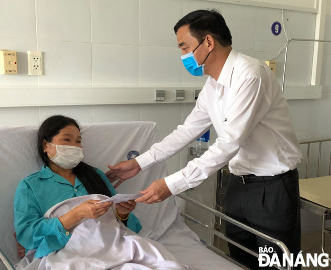 Vice Chairman Chinh giving spiritual encouragement and cash gift to a victim being treated at the Da Nang General Hospital