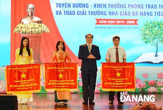 Authorised by the Prime Minister, municipal People's Committee Chairman Huynh Duc Tho 2nd, right) awarding the national government-granted Emulation Flag to three groups