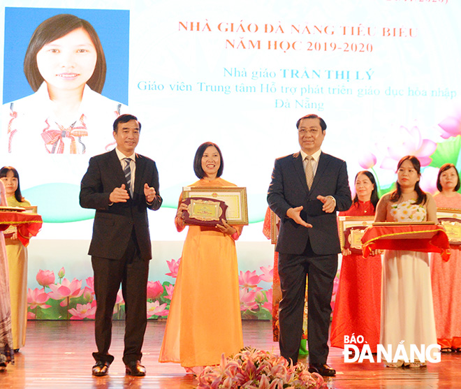 Municipal People's Committee Chairman Huynh Duc Tho (right) and People's Committee Permanent Vice Chairman Le Trung Chinh (left) honouring Da Nang's most outstanding teachers in the 2019 – 2020 academic year