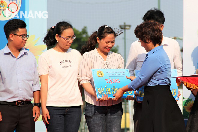 Da Nang Labour Federation Vice Chairwoman Dinh Thi Thanh Ha (right) handing presenting symbolic boards on house donations to poor employees.